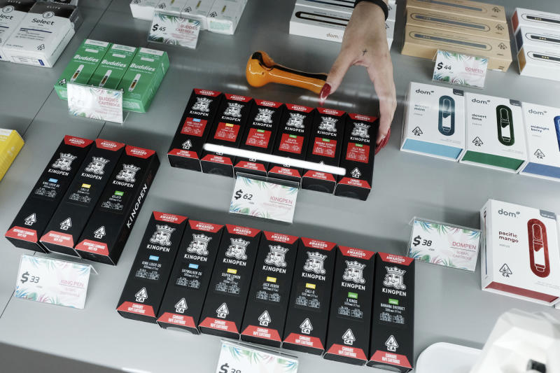This Tuesday, Sept. 10, 2019, photo shows a bud tender arranging a display of Kingpen cannabis vape cartridges at the Cannery Cannabis store in Los Angeles. Bootleggers eager to profit off unsuspecting consumers are mimicking popular vape brands, pairing replica packaging churned out in Chinese factories with untested, and possibly adulterated, cannabis oil produced in the state's vast underground market. (AP Photo/Richard Vogel)