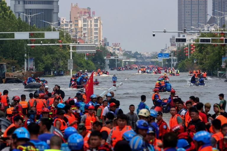 Rescuers evacuating residents at a flooded area in Weihui, Xinxiang city, in China's central Henan province