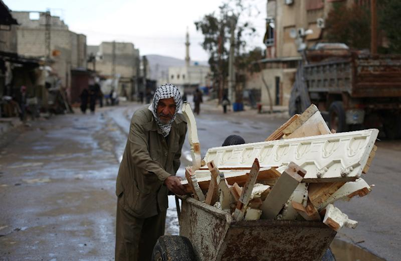 A Syrian man pushes a wheelbarrow loaded with pieces of wood collected from the rubble of collapsed buildings on March 21, 2015 in the rebel-held area of Douma, east of the capital Damascus (AFP Photo/Abd Doumany)