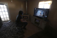 Javin Lujan Lopez, 17, a senior at Pojoaque High School, plays video games at his house on Monday, Feb. 22, 2021, in Española, N.M. He isn't sure what will happen after graduation. He's considering a welding certificate program at the local community college. He applied to universities in New Mexico and Colorado but feels like the pandemic year didn't allow him to put his best foot forward. (AP Photo/Cedar Attanasio)
