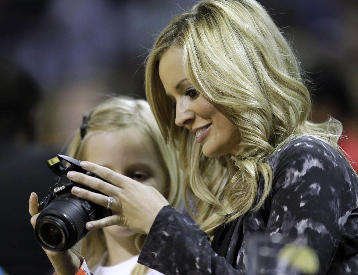 """Emily Maynard, right, looks at photos with her daughter, Ricki, left, in the second half of the Wizards' 97-91 win over the Charlotte Bobcats in an NBA basketball game in Charlotte, N.C., Sunday, April 3, 2011. Maynard was the winner of """"The Bachelor"""" reality series this season."""