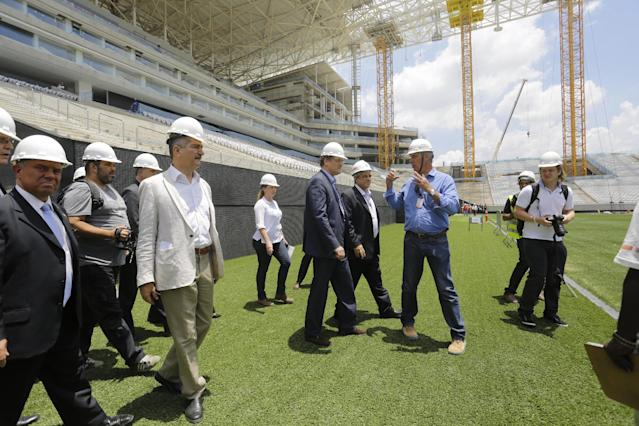 Jerome Valcke Secretary General of FIFA, center and Aldo Rebelo, Brazil Sports Minister, wearing light jacket, inspect Arena de Sao Paulo stadium, in Sao Paulo, Brazil, Monday, Jan. 20, 2014. Members of FIFA and the 2014 WCup Local Organizing Committee started today an inspection tour of stadiums in host cities across Brazil. (AP Photo/Nelson Antoine)