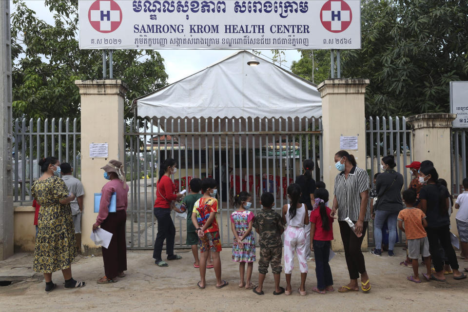 Children wait in front of Samrong Krom health center outside Phnom Penh, Cambodia, before their receive a shot of the Sinovac's COVID-19 vaccine Friday, Sept. 17, 2021. Prime Minister Hun Sen announced the start of a nationwide campaign to give COVID-19 vaccinations to children between the ages of 6 and 11 so they can return to school safely after a long absence due to measures taken against the spread of the coronavirus. (AP Photo/Heng Sinith)