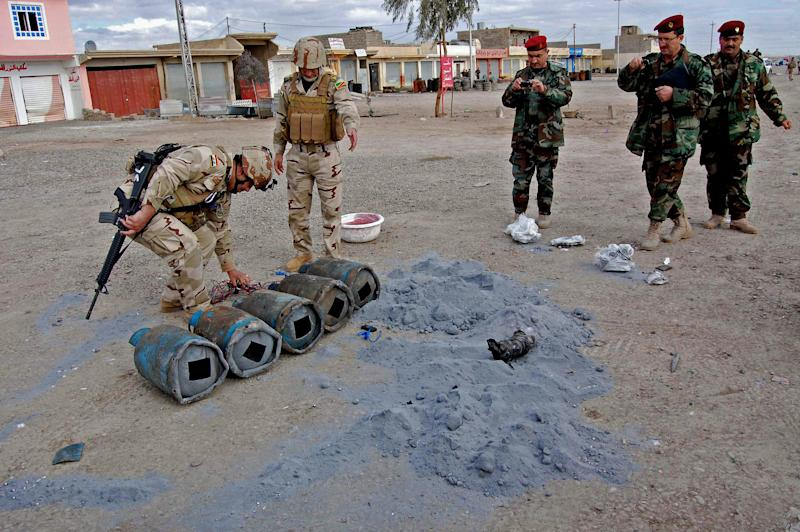 FILE - In this file photo taken on Jan. 16, 2012 Iraqi security forces inspect bombs at the scene of a car bomb attack outside the northern city of Mosul, 225 miles (360 kilometers) northwest of Baghdad, Iraq. Al-Qaida's Iraq arm is gaining strength in the restive northern city of Mosul, reviving its fundraising efforts through gangland-style shakedowns, feeding off anti-government anger and increasingly carrying out attacks with impunity. It is a worrying development for Iraq's third-largest city, one of its main gateways to Syria, as voters prepare to cast ballots for local leaders and al-Qaida makes a push to establish itself as a dominant force among the rebels fighting to topple the Syrian regime. (AP Photo, File)