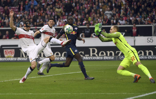 Stuttgart's Christian Gentner, left, and Leipzig's goal keeper Peter Gulacsi fight for the ball during a German Bundesliga socer match between VfB Stuttgart and RB Leipzig in Stuttgart, Germany, Sunday, March 11, 2018. (Marjan Murat/dpa via AP)