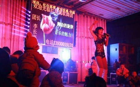 Children and adults watch a striptease show at a funeral in Cheng'an county, Hebei Province, China. - Credit: Zhang/Global Times