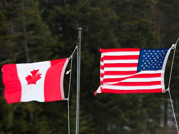<p>Canadian and American flags are seen at the US/Canada border on 1 March 2017, in Pittsburg, New Hampshire</p> ((AFP via Getty Images))