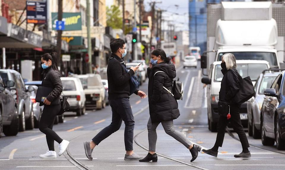 People cross a street in Melbourne during a lockdown against Covid-19.