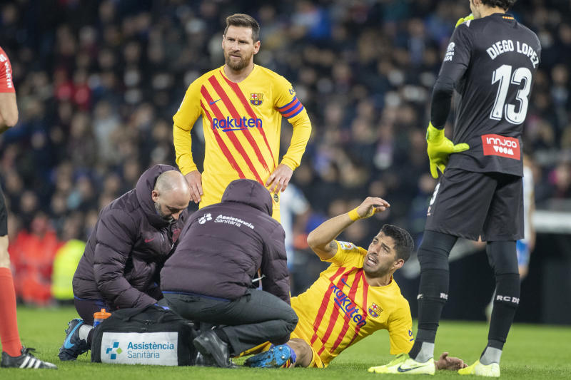 BARCELONA, SPAIN - January 04: Luis Suarez #9 of Barcelona reacts while receiving treatment for an injury watched by Lionel Messi #10 of Barcelona during the Espanyol V Barcelona, La Liga regular season match at RCDE Stadium on January 4th 2020 in Barcelona, Spain. (Photo by Tim Clayton/Corbis via Getty Images)
