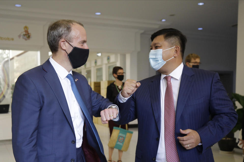 Britain's Foreign Secretary Dominic Raab, left, greets with an elbow bump with Cambodian's Environment Minister Say Sam Al after a meeting in Phnom Penh, Cambodia Wednesday, June 23, 2021. Raab is on his two-day official visit to Cambodia. (AP Photo/Heng Sinith)