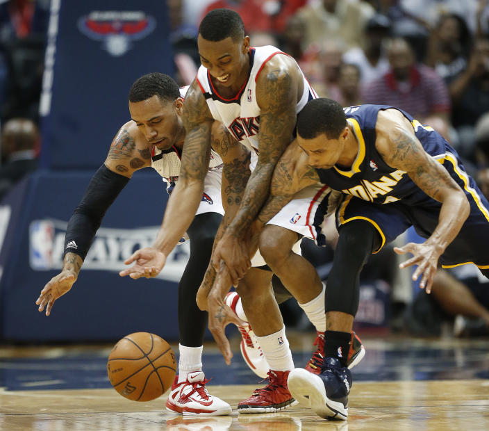 Atlanta Hawks forward Mike Scott, left, and guard Jeff Teague, center, chase a loose ball with Indiana Pacers forward Paul George, right, in the second half of Game 3 of an NBA basketball first-round playoff series on Thursday, April 24, 2014, in Atlanta. The Hawks won 98-85. (AP Photo/John Bazemore)