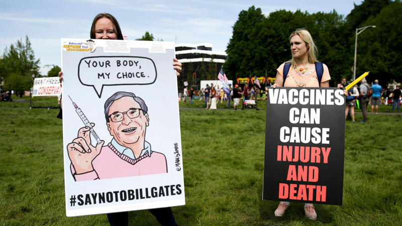 Two women hold anti-vaccination signs during a protest against Governor Jay Inslee's stay-at-home order outside the State Capitol in Olympia, Washington on May 9, 2020. (Jason Redmond/AFP via Getty Images)