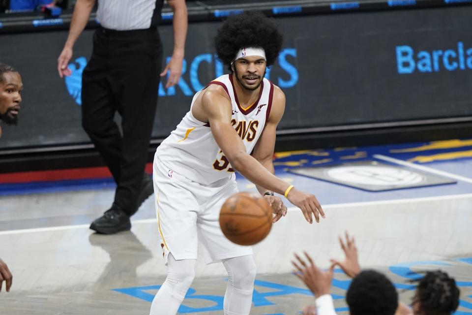 Cleveland Cavaliers' Jarrett Allen, center, passes to Isaac Okoro during the second half of an NBA basketball game against the Brooklyn Nets Sunday, May 16, 2021, in New York. (AP Photo/Frank Franklin II)