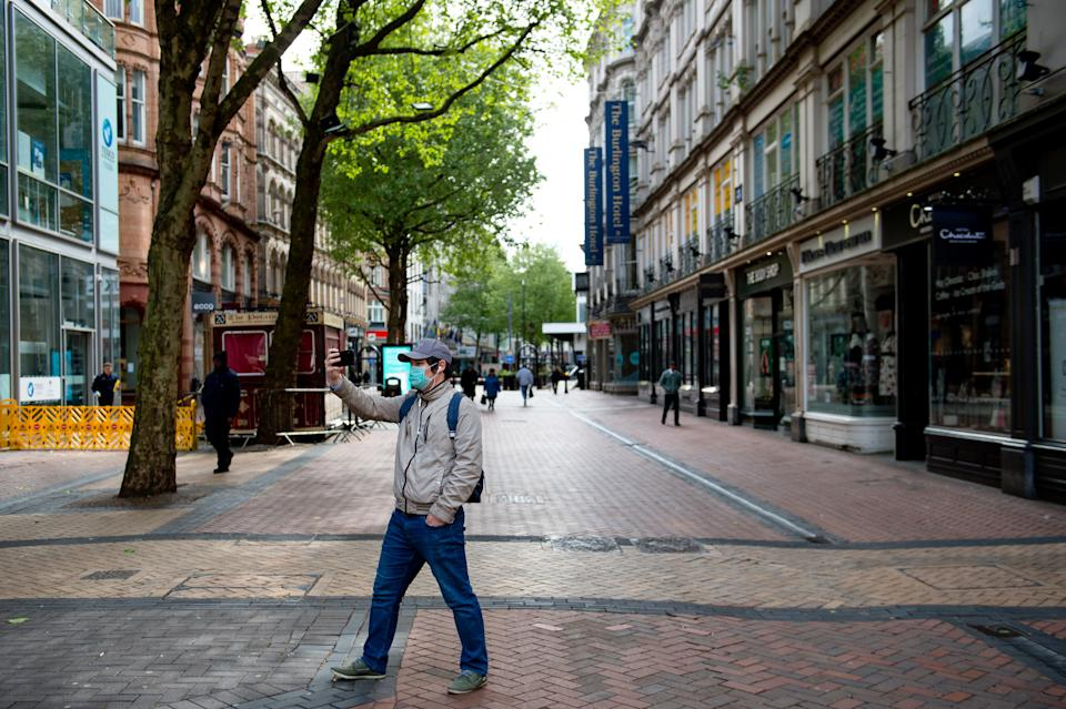 A pedestrian takes a photograph whilst walking on Hill Street in Birmingham city centre, as the UK continues in lockdown to help curb the spread of the coronavirus.
