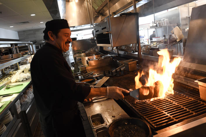 Cook Santiago Lopez flame broils meat for a hamburger during lunch at the Yard House in Lakewood, Colorado. A new Trump administration rule would allow employers to distribute servers' tips to back-of-house employees (Helen H. Richardson/The Denver Post via Getty Images)