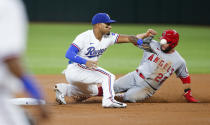 Texas Rangers second baseman Andy Ibanez (77) catches the throws from home as Los Angeles Angels David Fletcher (22) steals second during the first inning of a baseball game, Thursday, Aug. 5, 2021, in Arlington, Texas. (AP Photo/Brandon Wade)