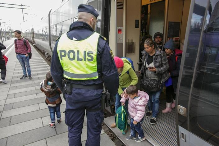 Swedish police gather a group of migrants off an incoming train in Malmo, Sweden, near the border with Denmark, on November 12, 2015 (AFP Photo/Stig-Ake Jonsson)