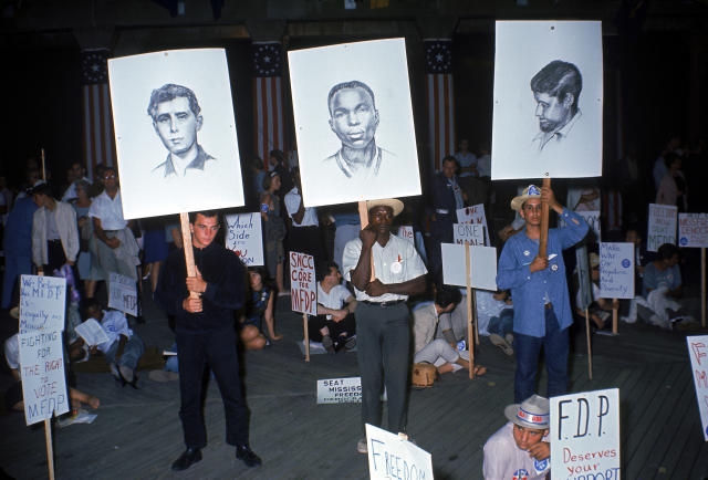 <p>Members of the Mississippi Freedom Democratic Party stand and hold up sketches of three slain civil rights volunteers (from left, Andrew Goodman, James Chaney, and Michael Schwerner) during a demonstration outside the Democratic National Convention, Atlantic City, New Jersey, August 1964. (Photo: Ralph Crane/The LIFE Picture Collection/Getty Images) </p>