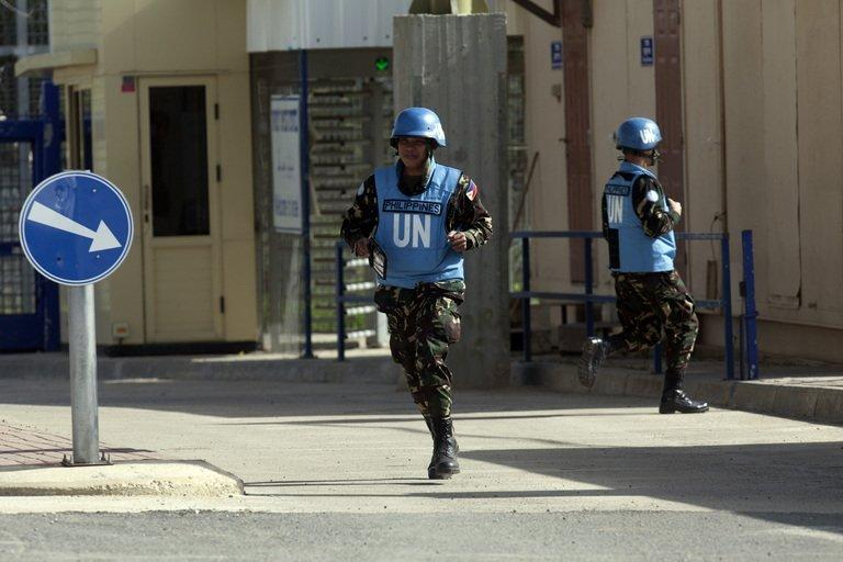 Filipino UN peacekeepers cross the Quneitra checkpoint between Israel and Syria in the Golan Heights on March 9, 2013