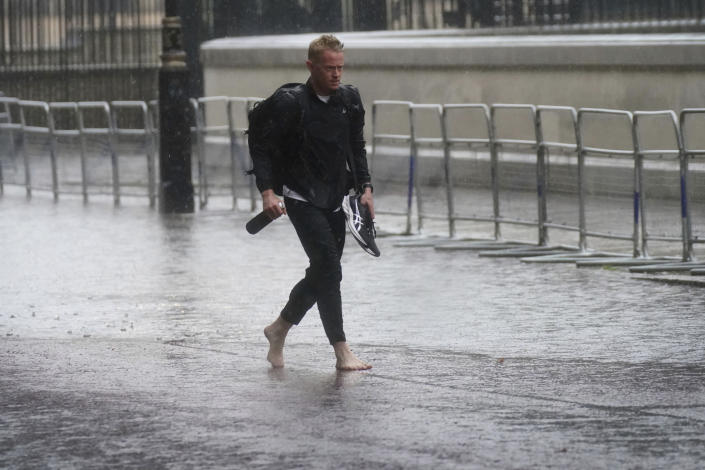 A man walks in bare feet through flood water in Horse Guards Road in central London, Sunday July 25, 2021. Thunderstorms bringing lightning and torrential rain to the south are set to continue until Monday it is forecast. (Victoria Jones/PA via AP)