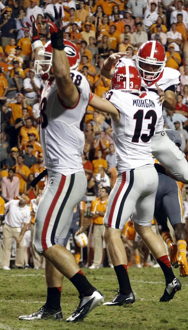 CORRECTS PLAYER AT REAR TO ADAM ERICKSON, INSTEAD OF JAY ROME - Georgia place kicker Marshall Morgan (13) celebrates Adam Erickson, rear, as Arthur Lynch (88) holds up his hands in overtime of an NCAA college football game against Tennessee on Saturday, Oct. 5, 2013, in Knoxville, Tenn. Georgia won 34-31. (AP Photo/Wade Payne)