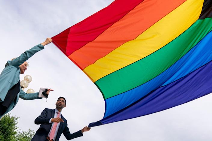 Energy Secretary Jennifer Granholm and Department of Energy Chief of Staff Tarak Shah, right, help raise the Progress Pride Flag outside the Department of Energy in Washington, Wednesday, June 2, 2021. Shah is the first person of color, first Indian-American and first openly LGBTQ person to serve as Chief of Staff for D.O.E.