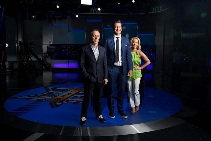 """Two men and a woman stand on the set of Fox News series """"The Five"""""""