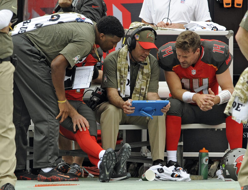 Injured Tampa quarterback Jameis Winston, left, and coach Mike Bajakian, center, work with Ryan Fitzpatrick during a game in November. (AP)
