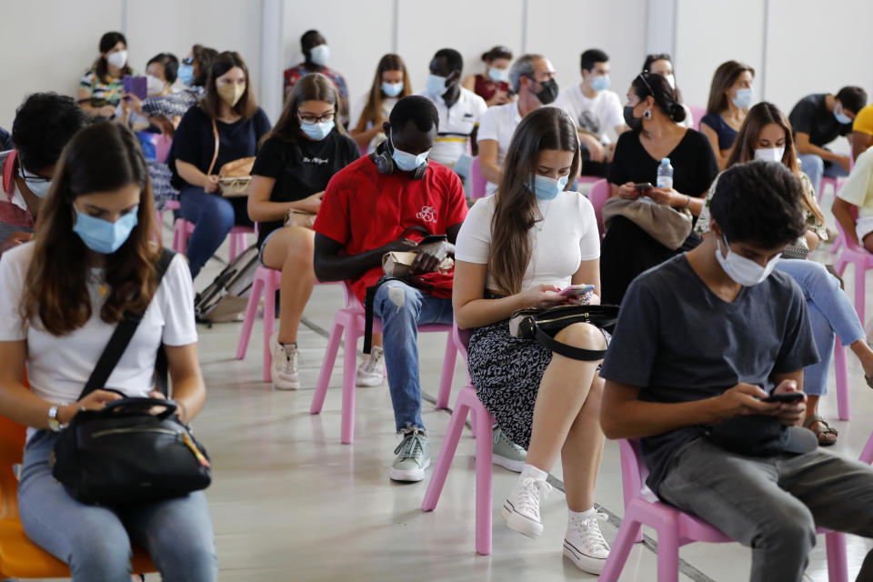 People fill a recovering room after receiving the coronavirus vaccine at a vaccination center in Lisbon, Saturday, Sept. 11, 2021. As Portugal nears its goal of fully vaccinating 85% of the population against COVID-19 in nine months, other countries want to know how it was able to accomplish the feat. A lot of the credit is going to Rear Adm. Henrique Gouveia e Melo. (AP Photo/Armando Franca)