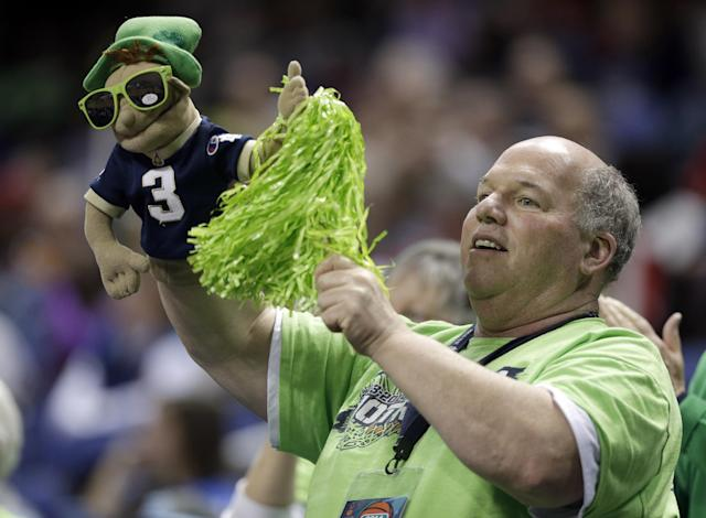 A Notre Dame fan cheers during the first half of an NCAA college basketball game between Notre Dame and Florida State at the Atlantic Coast Conference tournament in Greensboro, N.C., Friday, March 7, 2014. (AP Photo/Chuck Burton)