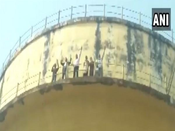 The Hardoi family atop the water tank on Sunday, threatening to commit suicide. (Photo/ANI)
