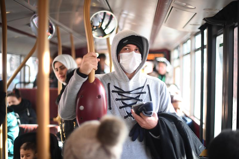 A pedestrian wears a protective facemask while taking a bus in Westminster, London, on the day that Health Secretary Matt Hancock said that the number of people diagnosed with coronavirus in the UK has risen to 51. (Photo by Victoria Jones/PA Images via Getty Images)
