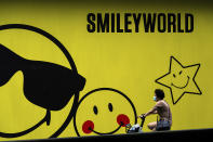 A woman wearing a face mask to help curb the spread of the coronavirus bicycles past a smiley faces billboard outside a shopping mall in Beijing, Monday, July 19, 2021. (AP Photo/Andy Wong)