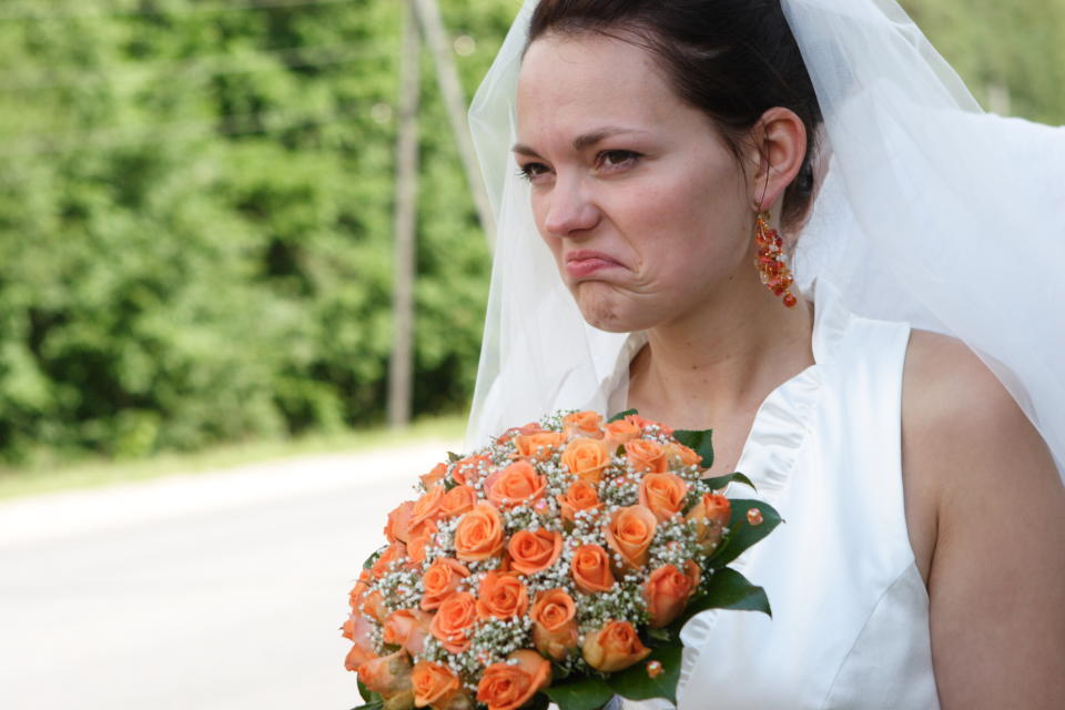 An unhappy bride wearing a white dress and holding a bouquet of orange roses while making an angry expression