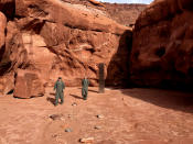 This Nov. 18, 2020 photo provided by the Utah Department of Public Safety shows Utah state workers walking near a metal monolith in the ground in a remote area of red rock in Utah. The smooth, tall structure was found during a helicopter survey of bighorn sheep in southeastern Utah, officials said Monday. State workers from the Utah Department of Public Safety and Division of Wildlife Resources spotted the gleaming object from the air and landed nearby to check it out. The exact location is so remote that officials are not revealing it publicly, worried that people might get lost or stranded trying to find it and need to be rescued. (Utah Department of Public Safety via AP)