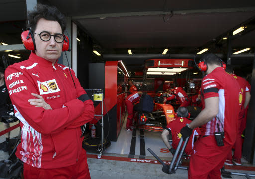 Ferrari team principal Mattia Binotto, left, stands in front of Sebastian Vettel's garage during the first practice session of the Australian Grand Prix in Melbourne, Australia, Friday, March 15, 2019. The first race of the year is Sunday. (AP Photo/Rick Rycroft)