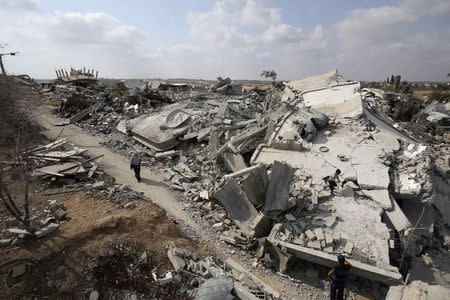 Palestinian woman walks past the ruins of houses which witnesses said were destroyed during the Israeli offensive in Johr El-Deek village near the central Gaza Strip