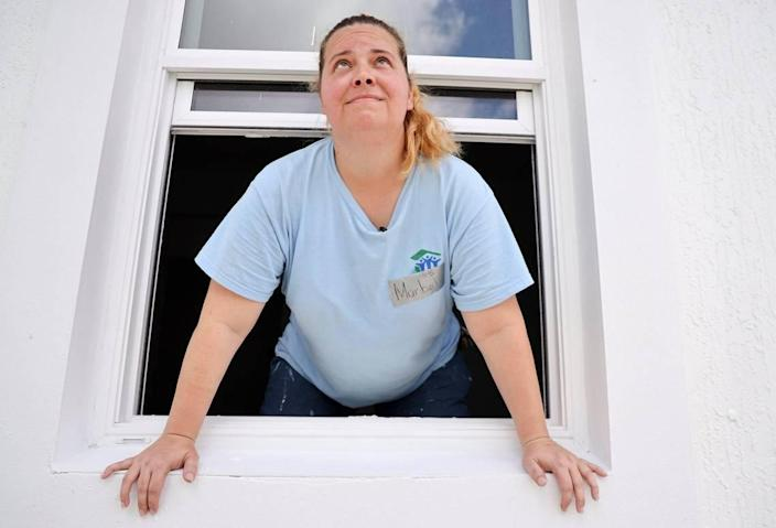 Maribel Gonzalez, 41, looks out the window of her new Habitat for Humanity of Greater Miami home in South Miami-Dade's Goulds neighborhood. Gonzalez and seven other new soon-to-be homeowners are helping hammer together their houses during Habitat's annual Blitz Build. The nonprofit recently marked 30 years in operation.