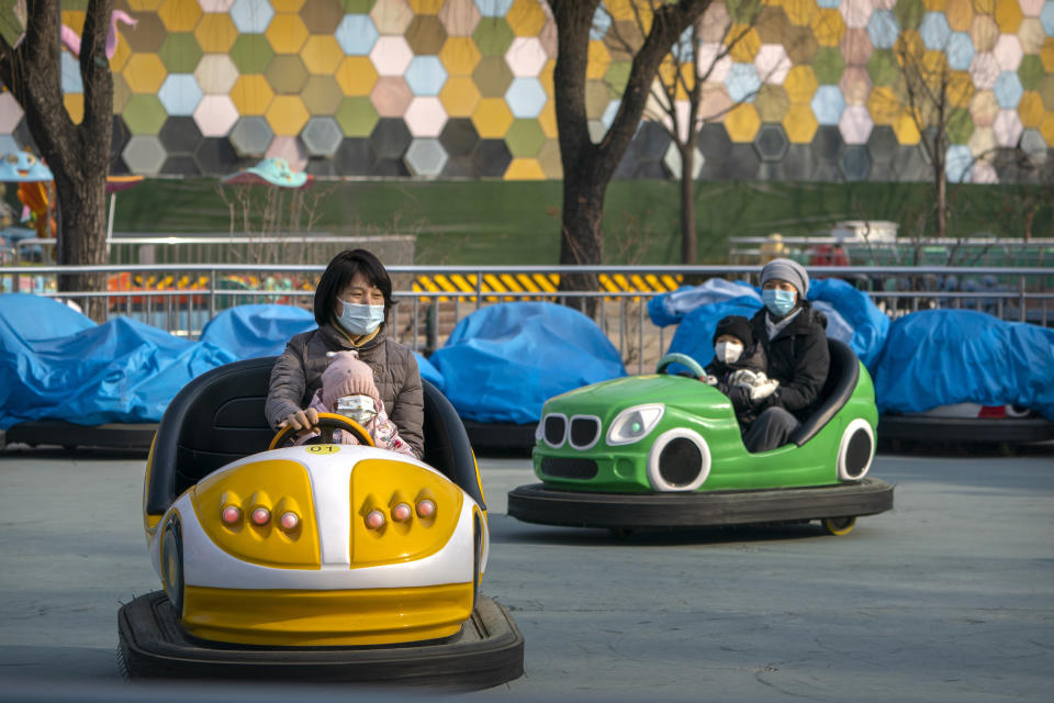 People wearing face masks to protect against the spread of the coronavirus ride on bumper cars at a public park in Beijing, Saturday, Jan. 2, 2021. Wary of another wave of infections, China is urging tens of millions of migrant workers to stay put during next month's Lunar New Year holiday, usually the world's largest annual human migration. (AP Photo/Mark Schiefelbein)