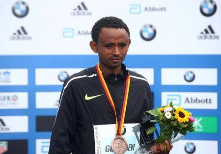 Athletics - Berlin Marathon - Berlin, Germany - September 24, 2017 Ethiopia's Mosinet Geremew celebrates with a trophy after finishing third in the men's race REUTERS/Michael Dalder