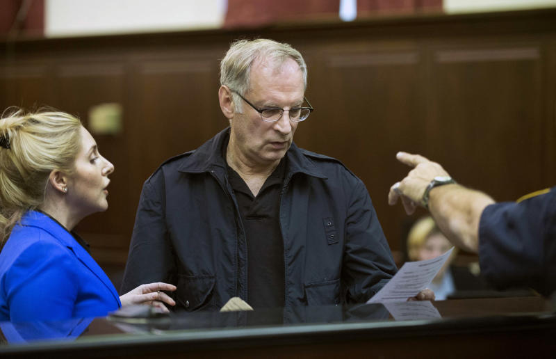 Bernhard Goetz, center, stands with attorney Danielle Iredale, as he is arraigned in Manhattan criminal court, in New York, Saturday, Nov. 2, 2013. Subway vigilante Goetz, who ignited a national furor over racism and gun control after he shot four panhandling youths on a train in the 1980s, was arrested on drug charges. (AP Photo/New York Post, Steven Hirsch, Pool)