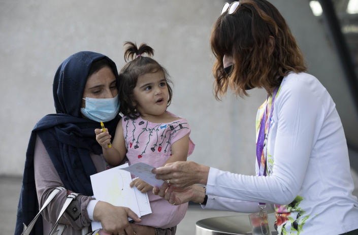 A volunteer interacts with a child evacuated from Kabul, Afghanistan at Washington Dulles International Airport, in Chantilly, Va., on Saturday, Aug. 28, 2021. (AP Photo/Gemunu Amarasinghe)