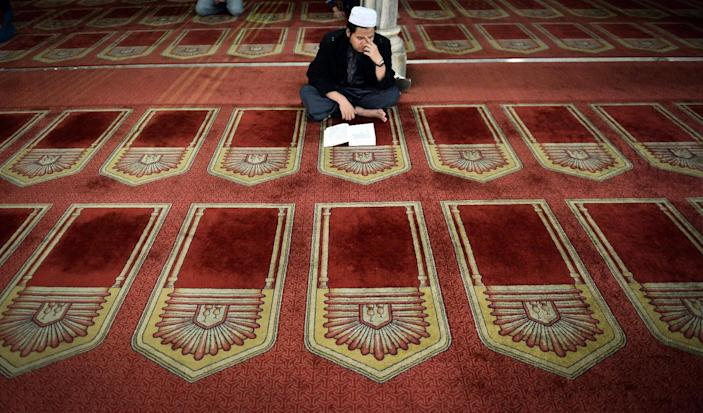 An Egyptian man reads from the Koran inside Al-Azhar mosque in the old city of Cairo on December 20, 2014 (AFP Photo/Mohamed el-Shahed)