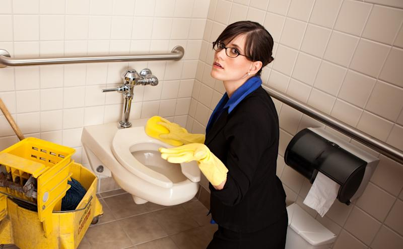 A businesswoman unhappy that she has to clean a toilet.