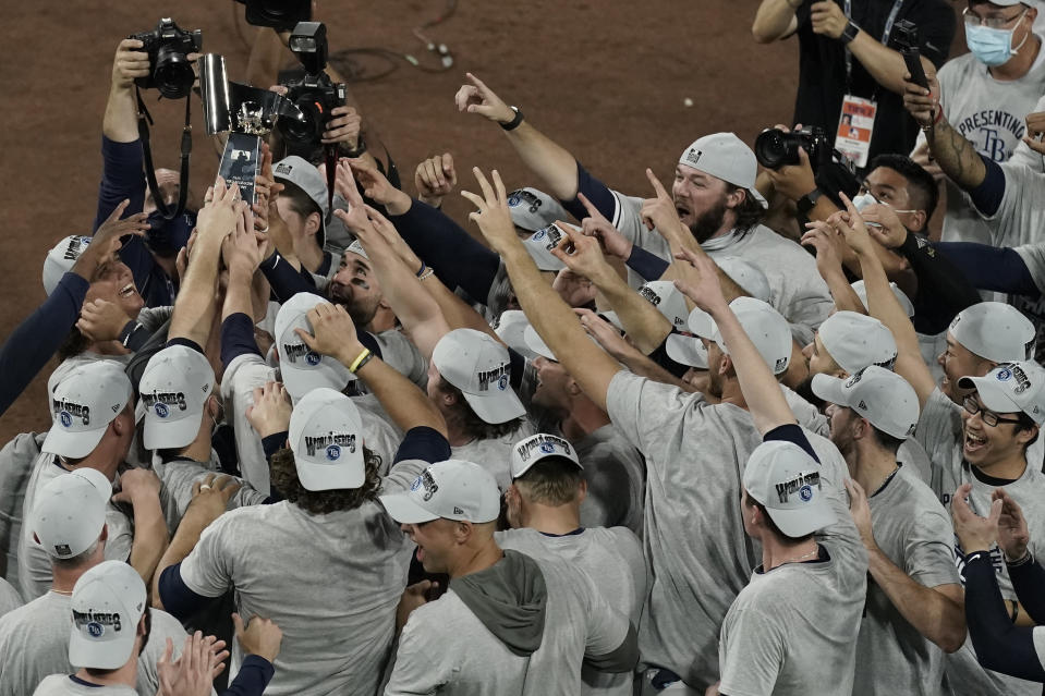 Tampa Bay Rays hold the American League championship trophy following their victory against the Houston Astros in Game 7 of a baseball American League Championship Series, Saturday, Oct. 17, 2020, in San Diego. The Rays defeated the Astros 4-2 to win the series 4-3 games. (AP Photo/Jae C. Hong)