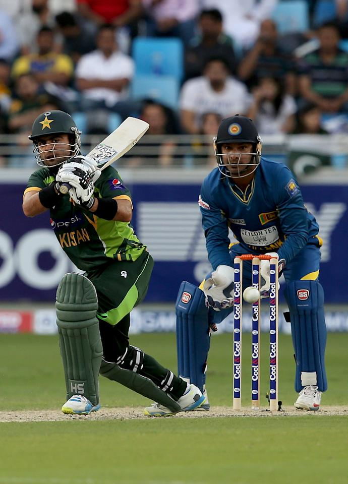 DUBAI, UNITED ARAB EMIRATES - DECEMBER 20:  Ahmed Shazad of Pakistan bats as Kumar Sangakkara of Sri Lanka looks on during the second One-Day International (ODI ) match between Sri Lanka and Pakistan at the Dubai Sports City Cricket Stadium on December 20, 2013 in Dubai, United Arab Emirates.  (Photo by Francois Nel/Getty Images)