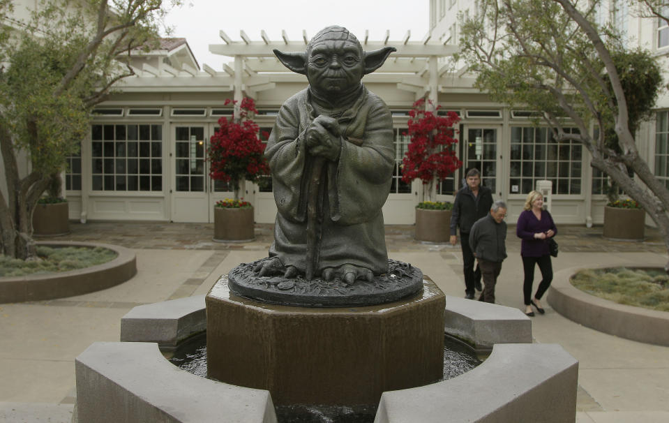 <p> People walk past a fountain showing the Yoda character from the Star Wars movies outside of Lucasfilms headquarters in San Francisco, Tuesday, Oct. 30, 2012. The Walt Disney Co. announced Tuesday that it was buying Lucasfilm Ltd. for $4.05 billion. (AP Photo/Jeff Chiu) </p>