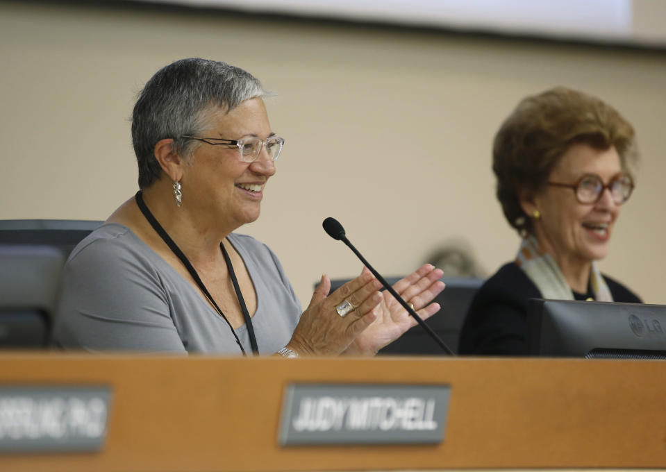 FILE - In this Sept. 25, 2015, file photo, Mary Nichols, left, chair of the California Air Resources Board, applauds after the board restored ambitious rules to cut transportation fuel emissions 10 percent within five years, during a hearing in Sacramento, Calif. Nichols' term leading the board ends in December. She's held the role since 2007 after an earlier stint as chair in the early 1980s. (AP Photo/Rich Pedroncelli, File)