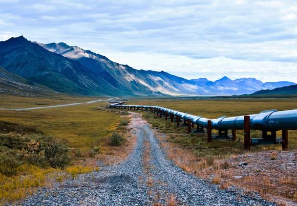 Pipeline next to gravel road stretches into the distance, with mountains in the background