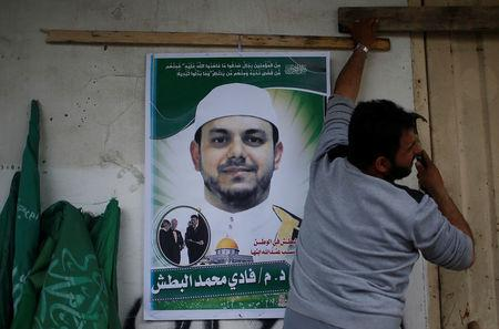 A man hangs a poster depicting Palestinian electrical engineer Fadi al-Batash, who was shot to death in Malaysia, on his family house in the northern Gaza Strip